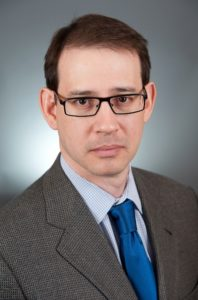 A person wearing glasses and a suit Description automatically generated with medium confidence